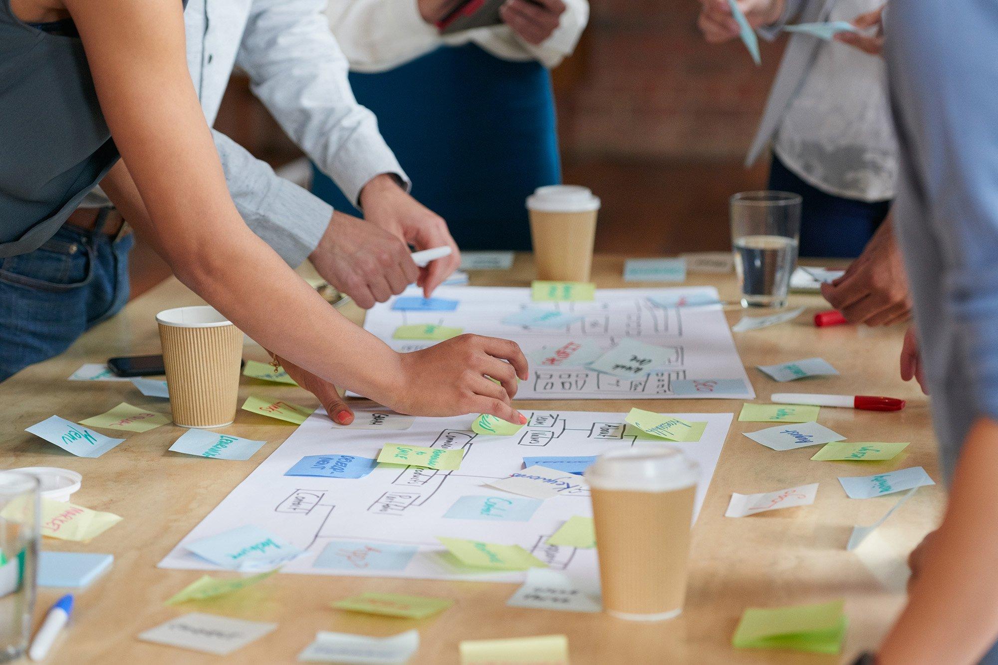 Brainstorming around desk with postits 2